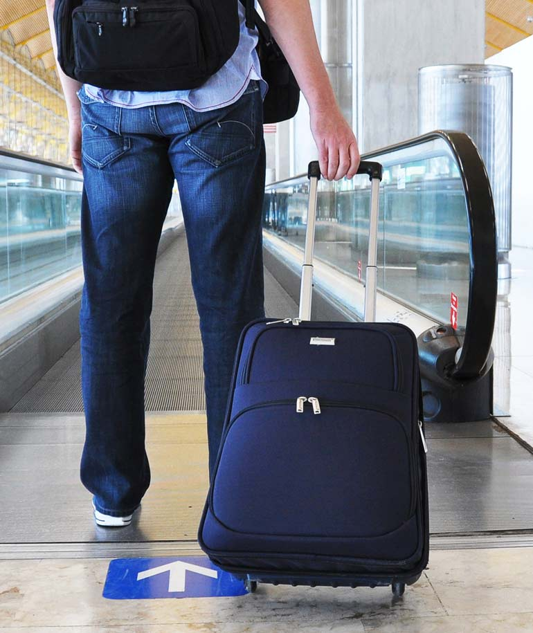 man standing with suitcase at airport