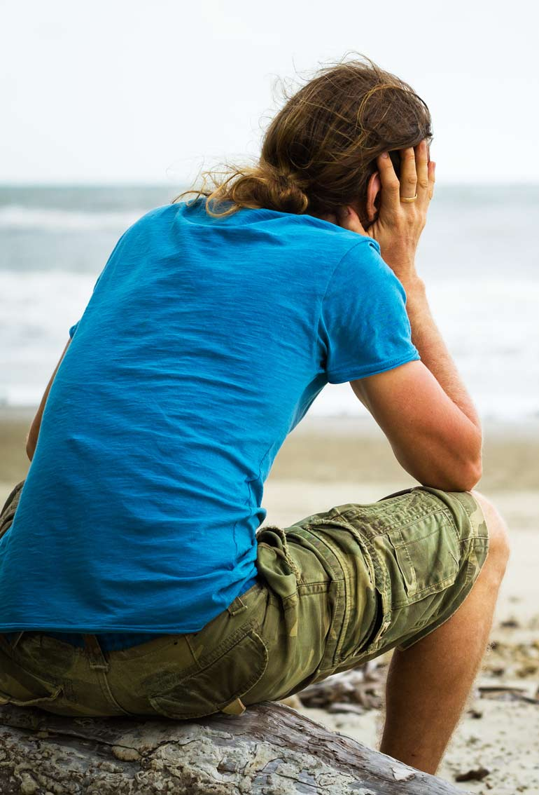 sad young man sitting by the beach