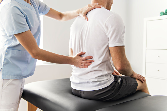 man sitting on table at physical therapy or chiropractor