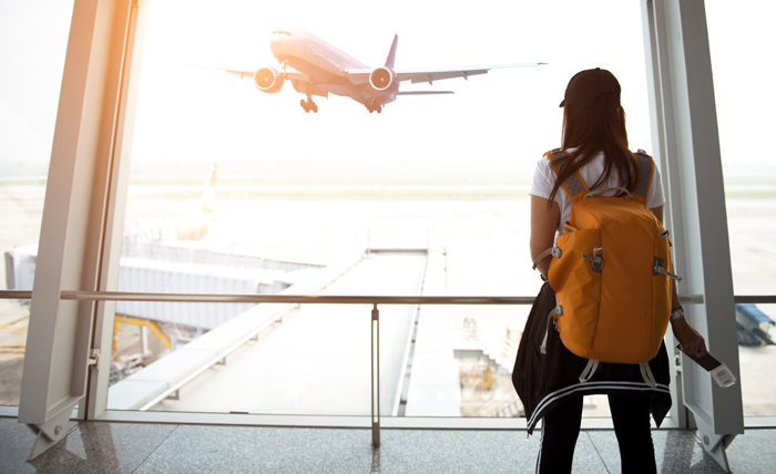 woman with orange backpack facing large window at airport - plane taking off - home