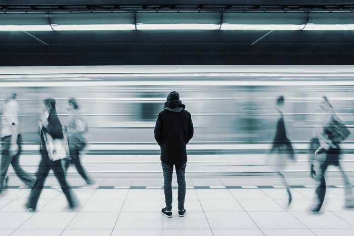 man standing on subway platform - long exposure - black and white - loneliness in sobriety