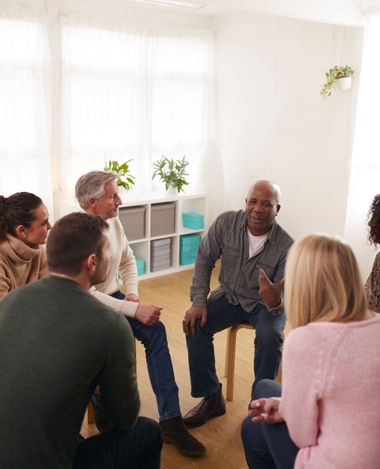 diverse group of adults talking in group therapy - intensive outpatient program - IOP